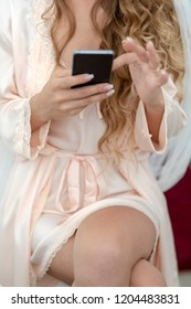 Beautiful blonde girl uses a smart phone while sitting on bed in her bedroom wearing a sexy lingerie.