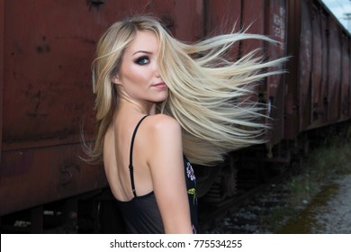 Beautiful blonde girl walking on rail tracks, romantic look, from back, wind tin the hair