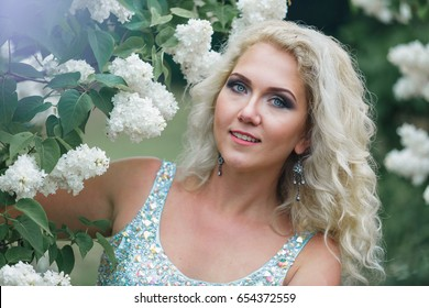 Beautiful blonde girl with wavy hair in a long blue dress posing in the summer garden  among the white lilacs