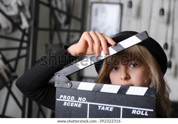Beautiful blonde girl wearing black hat and holding clapper board in studio