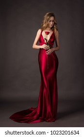 Beautiful blonde girl wearing a deep neckline red satin dress holding red rose in her hand on a grey background. Copy space. Advertising, fashion and commercial Design