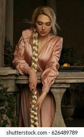 Beautiful blonde girl wearing pink dress with a long braid in the medieval interior.