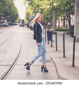 Beautiful blonde girl wearing ripped jeans and leather jacket posing in the city streets