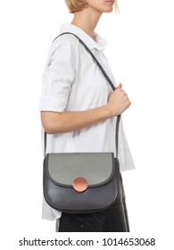 Beautiful blonde girl wearing a white shirt and dark pencil, with a gray leather bag on her shoulder, on a white background, shooting in the studio