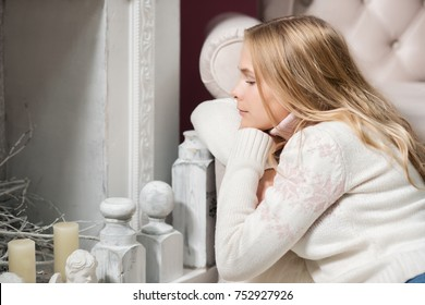 beautiful blonde girl in white jacket indoor decorated tree with toys