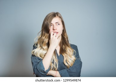 Beautiful blonde girl worries and bites nails, isolated on gray background