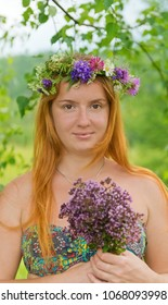 Beautiful blonde girl in a wreath of wild flowers with a bouquet of oregano in her hands.