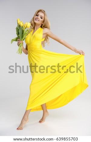 Beautiful blonde girl yellow dress flowers stock photo edit now beautiful blonde girl in yellow dress with flowers in hands mightylinksfo