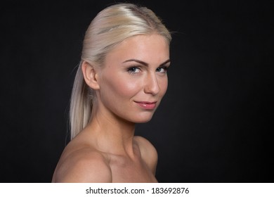 Beautiful blonde hair women isolated on black background looking at camera. Friendly close up. Studio shot.