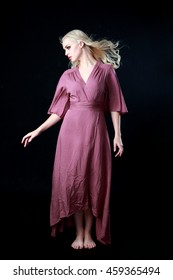 Beautiful blonde haired woman wearing a long flowing purple dress.   isolated on a black background.