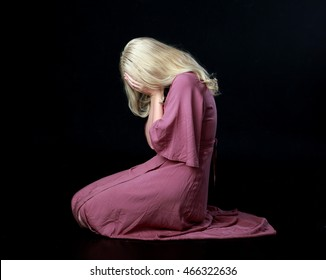 Beautiful blonde haired woman wearing a long flowing purple dress, kneeling on the ground.  isolated on a black background.