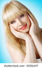 Beautiful blonde with hands on cheek over light blue background