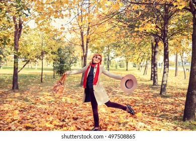 Beautiful blonde in a hat walking in the autumn park.