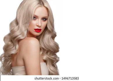 Beautiful blonde in a Hollywood manner with curls, natural makeup and red lips.. Beauty face and hair. Picture taken in the studio