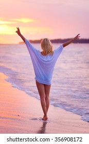 Beautiful blonde lady, arms rised in the sky, relaxing and enjoying vacations on the sandy tropical beach at sunset.