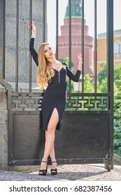 Beautiful blonde lady in black dress with decolletage at Park in Alexander Garden, Moscow, Russia