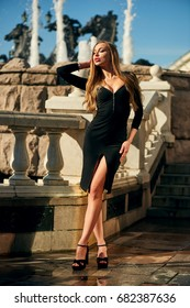 Beautiful blonde lady in black dress with decolletage at Park and Horses fountain in Alexander Garden at the Maneschnaja road, Moscow, Russia