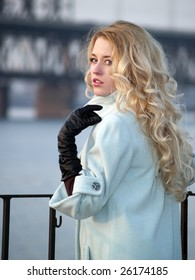 Beautiful blonde lady in overcoat on promenade