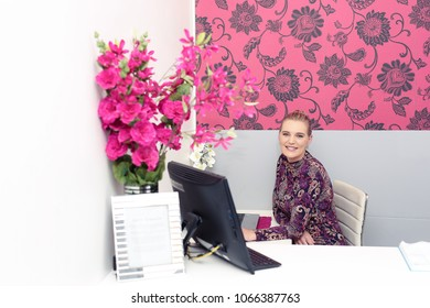 Beautiful blonde lady sitting at her desk at the office.