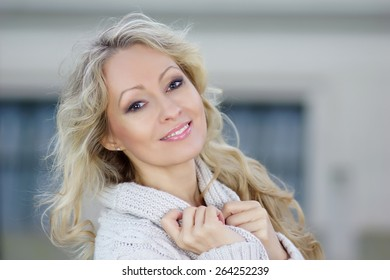 Beautiful blonde lady smile into camera on creamy background