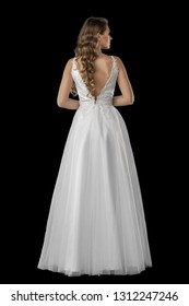 Beautiful blonde lady wearing a long white bridal gown. isolated on black background