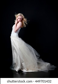 Beautiful blonde lady wearing a long white bridal gown. isolated on black background.