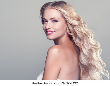 Beautiful blonde long curly hair woman with beauty makeup and healthy skin female fashion portrait