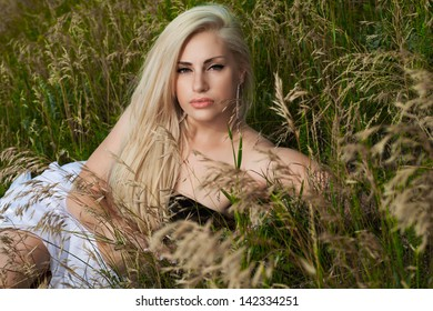 beautiful blonde with long hair on the  rocks and grass