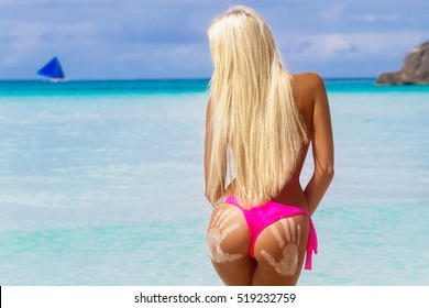 Beautiful blonde with long hair on a tropical beach with his back to the viewer. At the bottom of a girl prints sand men's hands. Summer vacation concept.