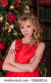 Beautiful blonde in a long red dress at the Christmas tree. Portrait of a girl with floral wreath on her head