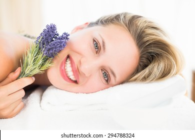 Beautiful blonde lying on massage table with lavanda at the health spa