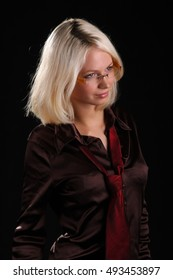 beautiful blonde in a men's tie and glasses ob black background
