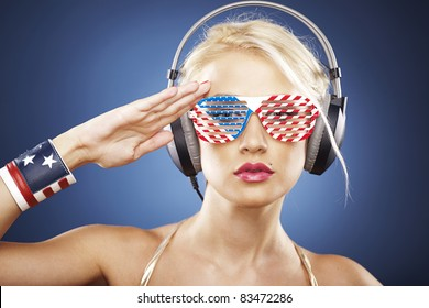 Beautiful blonde model with headphones and American inspired grid glasses dressed in gold swimwear saluting the flag.