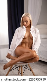 Beautiful blonde model posing nude near the chair in the white shirt - close up portrait