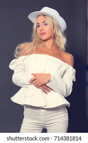 Beautiful blonde model posing in a white suit on a gray studio background in a hat