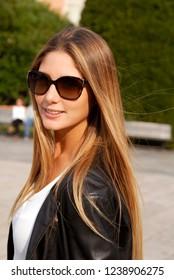 Beautiful blonde model walking on street style wearing black jacket.