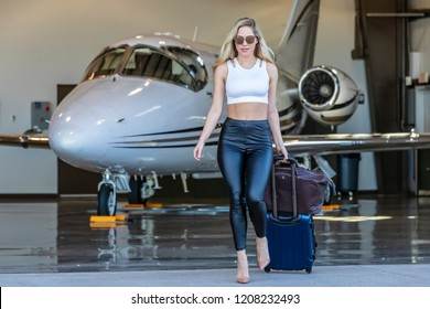 A beautiful blonde model walks away from her private jet as she heads out on her holiday