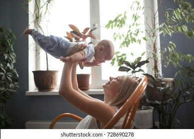 beautiful blonde mom with her baby son hugging and talking on an armchair from rattan at home, emotional lifestyle, selective focus and toning