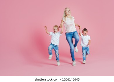 Beautiful blonde mom with two happy sons. Young woman and two baby boys, Jump on pink background