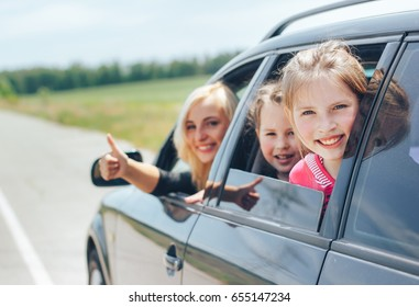 Beautiful blonde mom while driving a car with her children