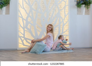 beautiful blonde mother and cute little daughter having fun and playing in fashionable spacious apartment with a stylish design in green, grey and white pastel colors