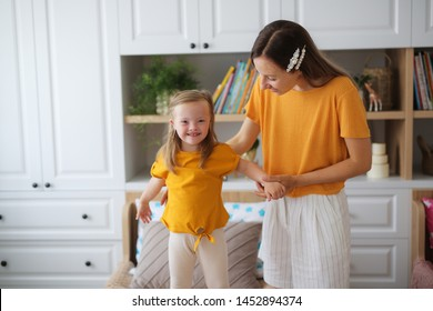 beautiful blonde mother and daughter with Down syndrome, mother supports the girl. jumping on the bed in the bedroom. Yellow T-shirts and Scandinavian interior