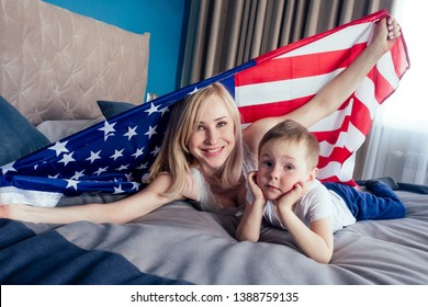 beautiful blonde mother and son lying on the bed in the bedroom holding american flag in a comfortable apartment safe house.4th july independence day celebration concept and learning English language