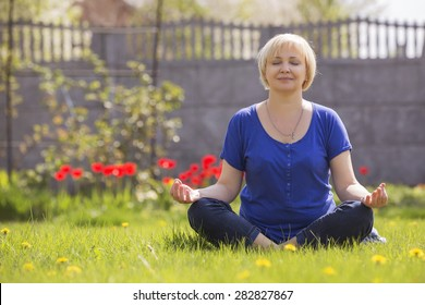 Beautiful blonde old senior woman relaxing on a grass in park in yoga meditation. casual outfit. copy space