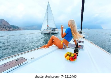 A beautiful blonde on a yacht drinks champagne and eats fruit, on the background of another yacht