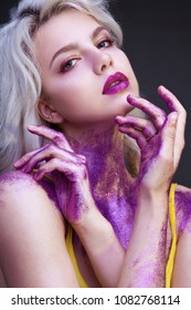 Beautiful blonde passionately posing in front of the camera.  Make-up with purple sequins