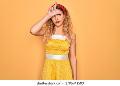 Beautiful blonde pin-up woman with blue eyes wearing diadem standing over yellow background making fun of people with fingers on forehead doing loser gesture mocking and insulting.