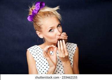 Beautiful blonde pinup woman eating sweet cake, looking at camera.