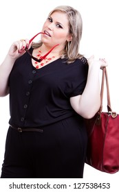 Beautiful blonde plus size woman, a model, wearing black and with dark red accessories and holding a bag and generic sunglasses.