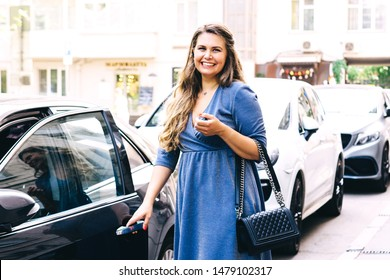 Beautiful blonde pregnant woman opens the driver's door of her car